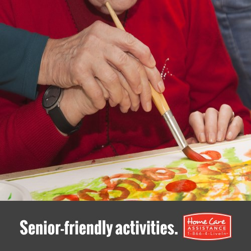 Caregiver Helping Senior Paint